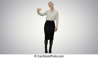 Young pretty businesswoman take selfie with cell phone on white background.