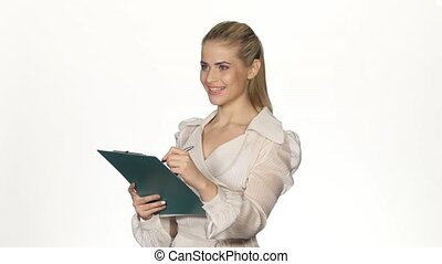 Young, pretty businesswoman writing notes. White