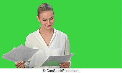 Young pretty businsswoman throws paper document pages on a Green Screen, Chroma Key.