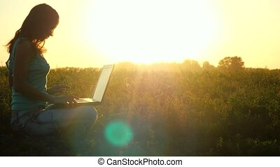 Young pretty caucasian brunette woman typing on a laptop outdoors at beautiful sunset sitting on the grass with amazing lense flare effects.