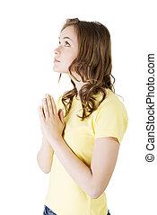 Young pretty caucasian girl praying