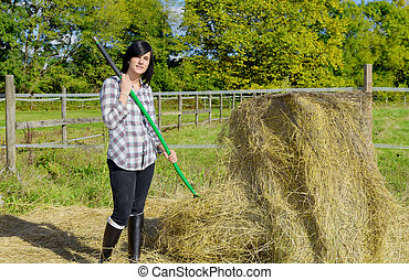 Young pretty country woman working on the farm, loading straw