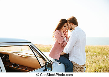 Young Pretty couple embracing while leaning on a vintage car