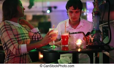 Young pretty couple flirt on date drinking cocktails smoking hookah at night club bar during party. 1920x1080