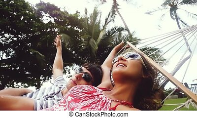Young pretty couple in sunglasses relaxing on hammock on ...