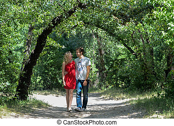 young pretty couple in the green summer park