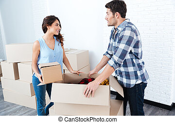 Young pretty couple unpacking in new flat
