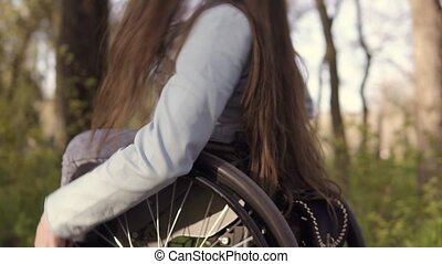 Young Pretty disabled woman in wheelchair walking in the...