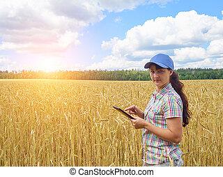 Young pretty farmer girl standing in yellow wheat field