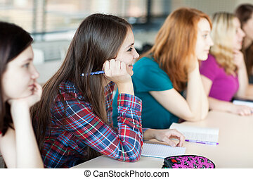 young pretty female college student sitting in a classroom
