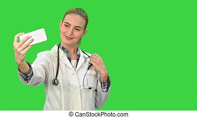 Young pretty female doctor makes selfie on smart phone on a Green Screen, Chroma Key.