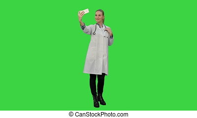 Young pretty female doctor makes selfie on smart phone smiling on a Green Screen, Chroma Key.