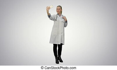 Young pretty female doctor makes selfie on smart phone smiling on white background.