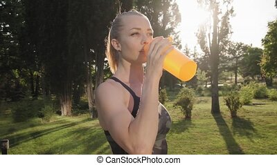 Young pretty female runner stopped to drink some water...