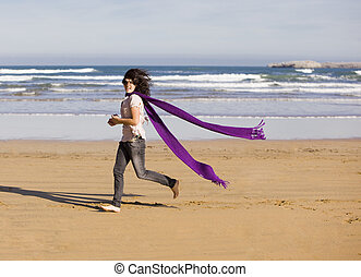 a young pretty girl with a scarf in a beach in a sunny beach