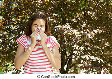 Young pretty girl blowing nose in front of tree. Spring allergy concept