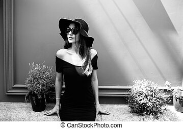 Young pretty girl in a black hat poses against the background of the wall