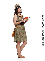 girl in summer dress and hat holding guidebook