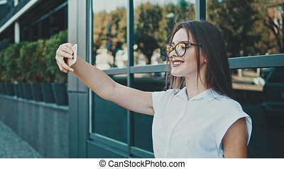 Young pretty girl in the business of clothing. During this time she makes a photo of Selphy on her phone.