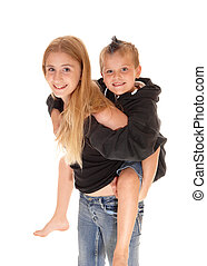 Young pretty girl is piggybacking little brother.