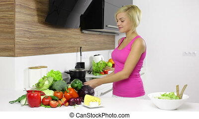 Blonde woman using tablet computer cook in her kitchen, young pretty girl looking for recipe and pick fresh raw vegetable products to prepare dinner home