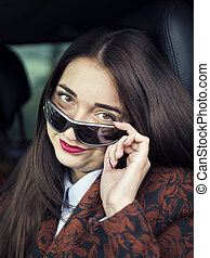 Young pretty girl sitting behind the wheel of a car