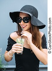 Young pretty girl standing near a cafe on the street and drinking cooled drink