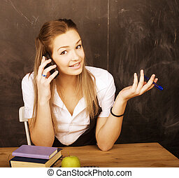young pretty girl student in classroom at blackboard