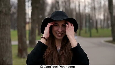 Young pretty girl with a black hat smiles happily into camera, close up, slow motion