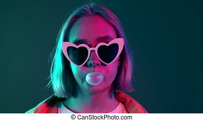 Young pretty girl with heart shaped glasses inflates the chewing bubble in glowing pink neon light of the city at night. Dyed violet hair. Hipster teenager concept.