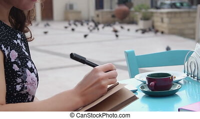 """Young pretty lady writing in notebook during lunch break in..."