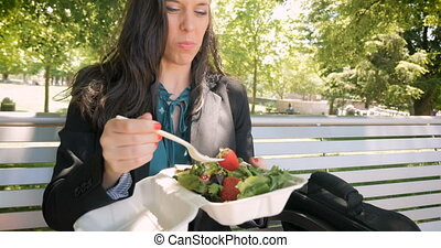 Young pretty millennial 30s woman eating healthy salad...