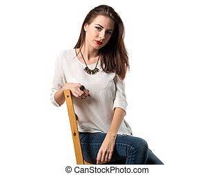 Young pretty model woman posing in studio on chair