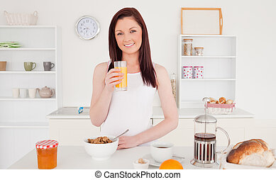 Young pretty red-haired woman drinking a glass of orange juice
