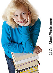 Young pretty schoolgirl is leaning on a pile of books and smiles. Isolated on white background.