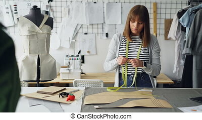 Young pretty seamstress is measuring clothing patterns with...