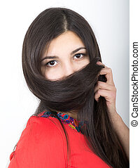 young pretty slim asian woman standing in a little red dress, She covers her face with her hair