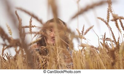 Young pretty smiling woman peeping out of ears of wheat ...