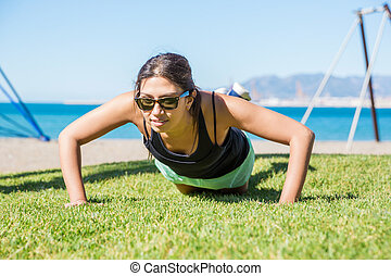Young pretty sportswoman doing push-ups on grass - Front...