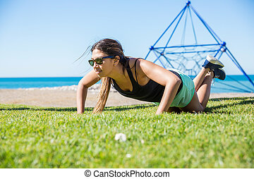 Young pretty sportswoman training push-ups outside -...