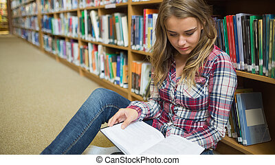 Young pretty student sitting on library floor reading book
