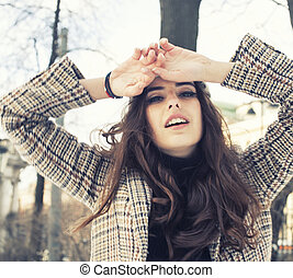 young pretty stylish modern girl outside on street, fashion coat, hairstyle, make up, lifestyle people concept