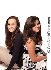 Pretty young teen girls that could be sisters of friends smiling, both with long brown hair on a white background