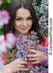 Young pretty woman among pink lilac