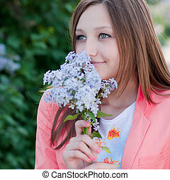 Young pretty woman smelling pink lilac