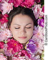 Young pretty woman among pink lilies