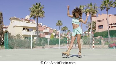 Young pretty woman dancing in roller skates