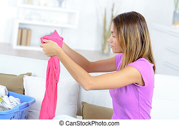 young pretty woman doing her laundry at home