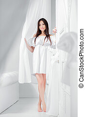 Young pretty woman dressed in a white dress.