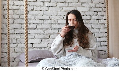 Young pretty woman drinking aroma coffee in bed at home....